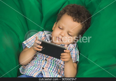 Little Boy Using Digital Device Modern Technology stock photo, Little boy lies using smartphone modern technology by Dmytro Sidelnikov