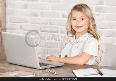 Little Girl Using Digital Device Modern Technology stock photo, Little girl sitting using laptop modern technology by Dmytro Sidelnikov