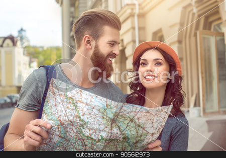 Young couple tourists city walk together vacation stock photo, Young couple woman and man tourists city walk together vacation holding map by Dmytro Sidelnikov