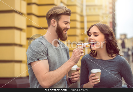 Young couple tourists city walk together vacation stock photo, Young couple woman and man tourists city walk together vacation eating by Dmytro Sidelnikov