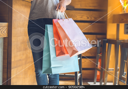 Young woman standing in a coffee shop leisure stock photo, Young female standing in a cafe indoors rest holding shopping bags by Dmytro Sidelnikov