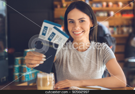 Young woman sitting in a coffee shop leisure stock photo, Young female sitting in a cafe indoors rest holding tickets by Dmytro Sidelnikov