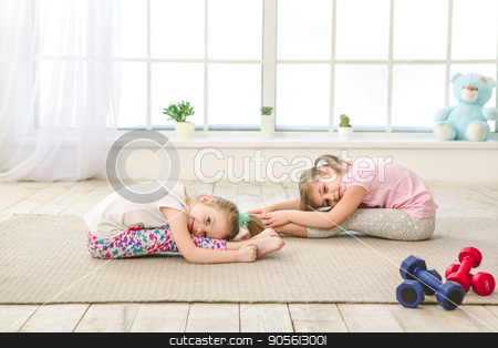 Little kids girls sisters exercise together indoors stock photo, Little children sisters girls exercise together in the morning at home by Dmytro Sidelnikov