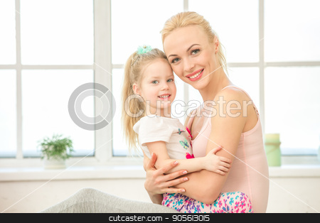 Young mother and daughter exercise together indoors stock photo, Young mother and little daughter exercise together in the morning at home by Dmytro Sidelnikov