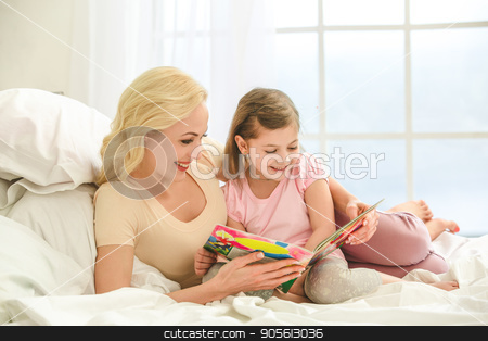 Young mother and daughter morning on bed indoors stock photo, Young mother and daughter morning on bed at home reading book by Dmytro Sidelnikov
