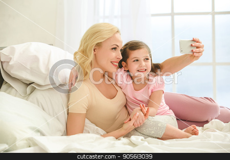 Young mother and daughter morning on bed indoors stock photo, Young mother and daughter morning on bed at home using digital device by Dmytro Sidelnikov