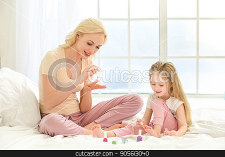 Young mother and daughter morning on bed indoors stock photo, Young mother and daughter morning on bed at home color nails by Dmytro Sidelnikov