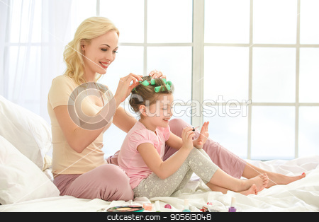 Young mother and daughter morning on bed indoors stock photo, Young mother and daughter morning on bed at home making hairstyle by Dmytro Sidelnikov