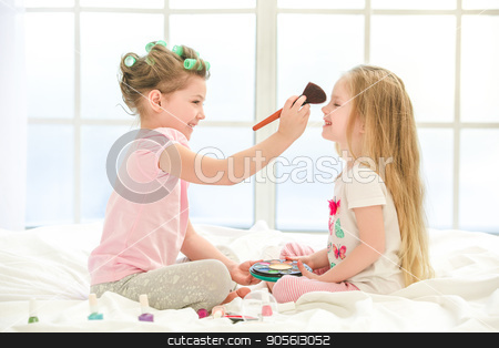 Little kids girls sisters doing makeup indoors stock photo, Little children girls sisters playing doing makeup on bed at home by Dmytro Sidelnikov