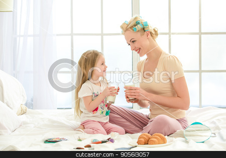 Young mother and daughter morning on bed indoors stock photo, Young mother and daughter morning on bed at home snack meal by Dmytro Sidelnikov
