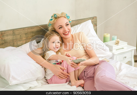 Young mother and daughter morning on bed indoors stock photo, Young mother and daughter morning on bed at home watching tv by Dmytro Sidelnikov
