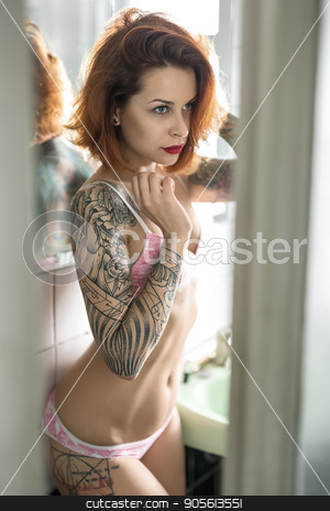 Tattooed girl in bathroom stock photo, Redhead girl with colorful tattoos stands in the bathroom with white tiled walls. She wears a rose lingerie. Beauty looks forward and holds left hand on the hair. Indoors. Vertical by bezikus