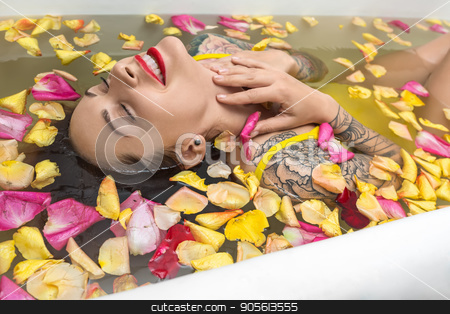 Tattooed girl posing in bath stock photo, Wet smiling girl with closed eyes and colorful tattoos lies in the white bath full of water with flower petals. She wears a yellow swimsuit. Beauty holds her hands on the neck. Indoors. Vertical by bezikus