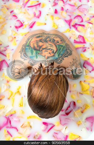 Tattooed girl relaxing in bath stock photo, Gorgeous girl with wet hair sits in the bath full of water with milk and flower petals. She has a colorful fox tattoo on the back and another tattoos on her shoulders. Top view photo. Indoors by bezikus
