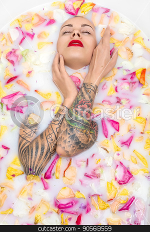 Tattooed girl posing in bath stock photo, Charming girl with closed eyes and parted lips lies in the bath full of water with milk and colorful flower petals. She has colorful tattoos on her arms. Top view photo. Indoors. Vertical by bezikus