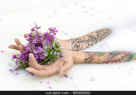 Girl's hands with tattoos and flowers stock photo, Hands of a girl with colorful tattoos on the surface of milk with flower petals. She holds multicolored flowers on her palms. Closeup. Indoors. Horizontal by bezikus