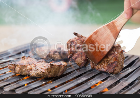 Chef grilling beef steaks on open flame BBQ. stock photo, Chef grilling a beef steak on open flame BBQ. by kasto