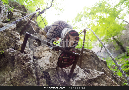 Woman climbing on the rocky route up the mountain. stock photo, Sporty active woman climbing on the rocky route up the mountain. Focus on the sole of the sports shoe. by kasto