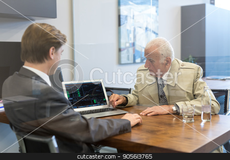 Financial advisor consulting senior client with his investment strategy. stock photo, Young financial advisor sitting in front of laptop, consulting senior client with his investment strategy. by kasto