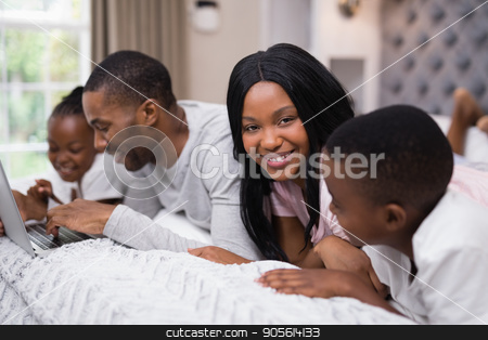 Portrait of smiling woman lying with family on bed stock photo, Portrait of smiling woman lying with family on bed at home by Wavebreak Media
