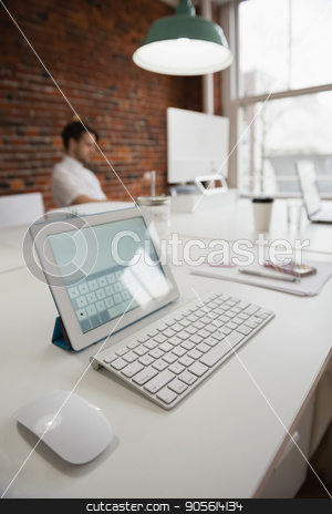 Digital tablet on desk stock photo, Digital tablet on desk in office by Wavebreak Media