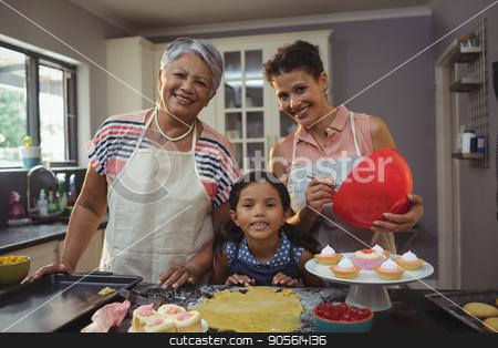 Happy family preparing desserts in kitchen stock photo, Portrait of happy family preparing desserts in kitchen at home by Wavebreak Media