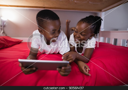 Smiling brother and sister using digital tablet while lying on bed stock photo, Smiling brother and sister using digital tablet while lying on bed at home by Wavebreak Media