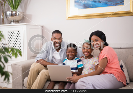 Happy family using laptop on sofa at home stock photo, Portrait of happy family using laptop on sofa at home by Wavebreak Media