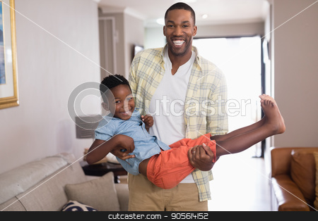 Playful father carrying son in living room stock photo, Playful father carrying son in living room at home by Wavebreak Media