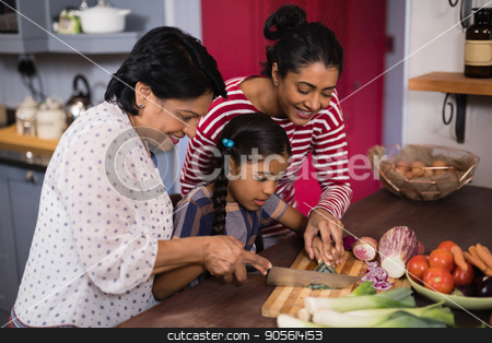 Multi-generation family preparing food together in kitchen stock photo, Multi-generation family preparing food together in kitchen at home by Wavebreak Media