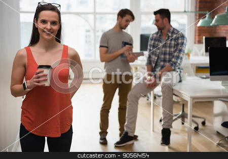 Portrait of executive holding coffee cup while colleague discussing in background stock photo, Portrait of executive holding coffee cup while colleague discussing in background at office by Wavebreak Media