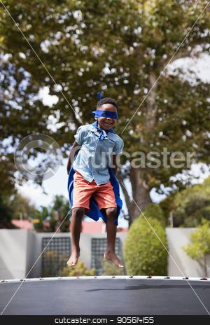 Boy in superhero costume jumping on trampoline stock photo, Full length of boy in superhero costume jumping on trampoline by Wavebreak Media