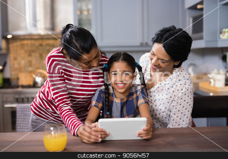 Portrait of girl with mother and grandmother using digital tablet in kitchen stock photo, Portrait of smiling girl with mother and grandmother using digital tablet in kitchen at home by Wavebreak Media
