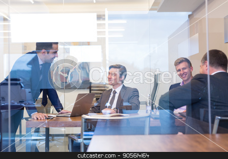 Business people sitting and brainstorming at corporate meeting. stock photo, Cheerful business people sitting and brainstorming at corporate meeting. Team work and business success concept. by kasto