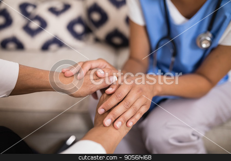Mid section of doctor touching patient hands stock photo, Mid section of doctor touching patient hands at home by Wavebreak Media