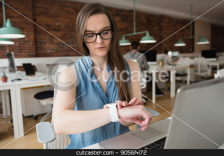 Female executive adjusting smart watch at desk stock photo, Female executive adjusting smart watch at desk in office by Wavebreak Media