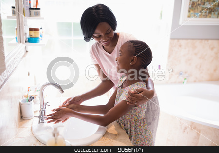 Mother and daughter washing hands at sink in bathroom stock photo, High angle view of mother and daughter washing hands at sink in bathroom by Wavebreak Media