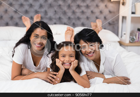 Portrait of cheerful multi-generation family lying on bed stock photo, Portrait of cheerful multi-generation family lying on bed at home by Wavebreak Media