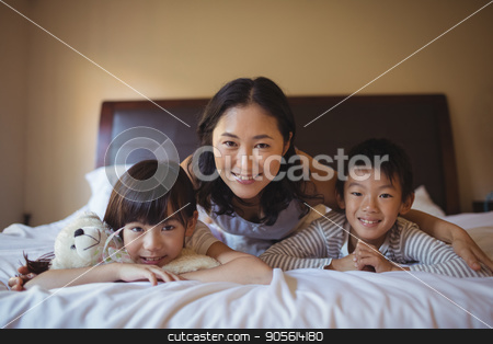 Mother with daughter and son relaxing on bed in bed room stock photo, Portrait of mother with daughter and son relaxing on bed in bed room at home by Wavebreak Media