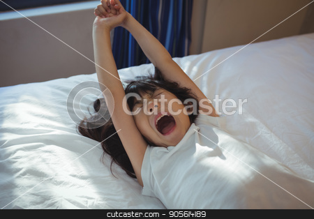Girl yawning on bed in the bed room stock photo, Girl yawning on bed in the bed room at home by Wavebreak Media