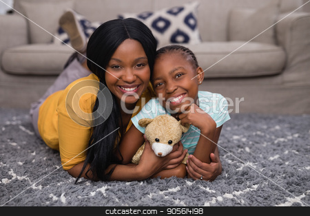 Mother and daughter holding teddy bear while lying on rug at home stock photo, Portrait of mother and daughter holding teddy bear while lying on rug at home by Wavebreak Media