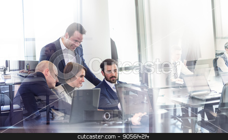 Business team working in corporate office. stock photo, Workplace in modern office with business people brainstorming. Businessman working on laptop during the meeting. by kasto