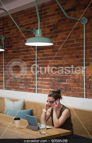 Business executive talking on mobile phone stock photo, Business executive talking on mobile phone in office by Wavebreak Media