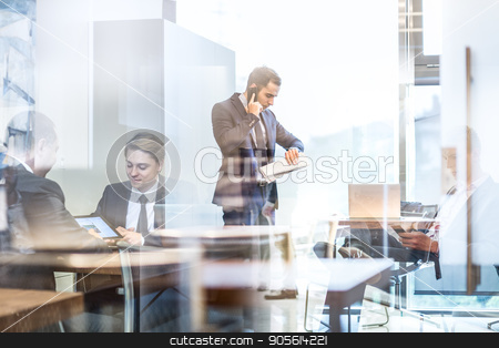 Businessman talking on a mobile phone on corporate office. stock photo, Businessman executive talking on mobile phone in modern corporate office, holding financial newspaper checking time on wriswatch. Glass reflection of business people meeting in office. Time is money. by kasto
