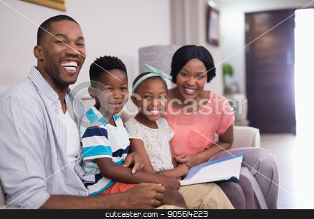 Cheerful family with magazine sitting on sofa at home stock photo, Portrait of cheerful family with magazine sitting on sofa at home by Wavebreak Media