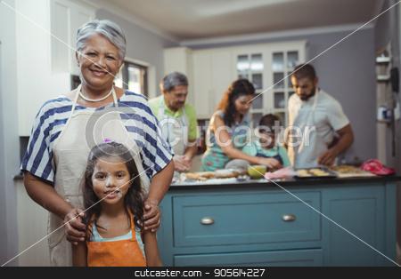Grandmother and granddaughter smiling at camera while family members preparing dessert in background stock photo, Grandmother and granddaughter smiling at camera while family members preparing dessert in background at home by Wavebreak Media