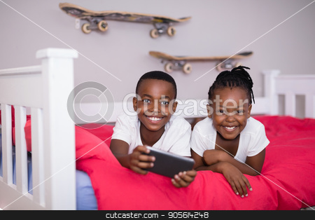 Happy siblings with mobile phone lying on bed at home stock photo, Portrait of happy siblings with mobile phone lying on bed at home by Wavebreak Media