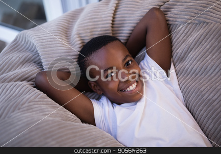 Smiling boy resting on couch at home stock photo, High angle view of smiling boy resting on couch at home by Wavebreak Media