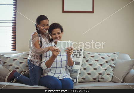 Mother and daughter using digital tablet in living room stock photo, Mother and daughter using digital tablet in living room at home by Wavebreak Media