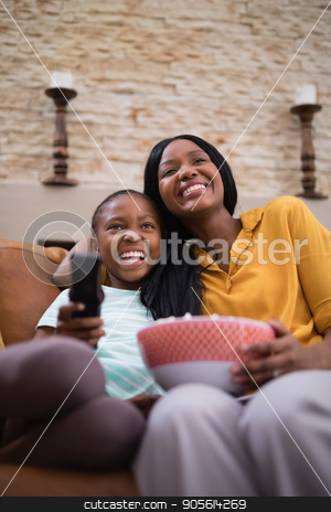 Cheerful mother and daughter enjoying television at home stock photo, Low angle view of cheerful mother and daughter enjoying television at home by Wavebreak Media